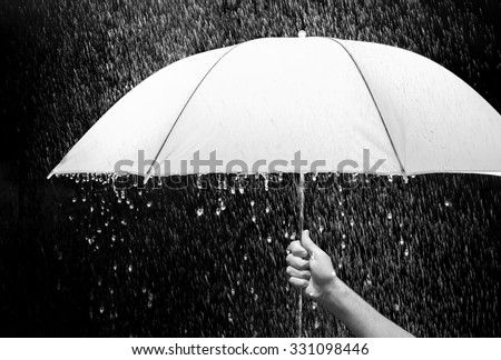 Hand holding an umbrella in rain, black background - business and fashion concept.