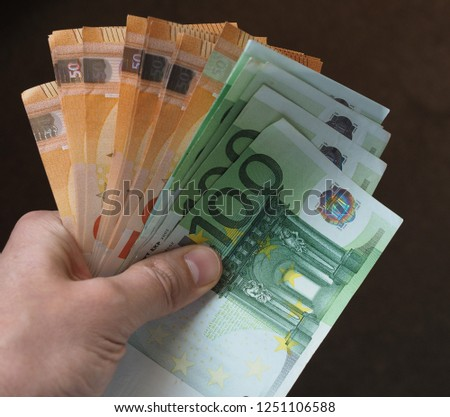 Hand holding and giving Euro banknotes money (EUR), currency of European Union