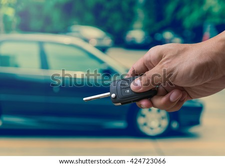 Hand holding and touching the keys over photo blurred of used car for open the door car, transportation and ownership concept, car key concept #424723066