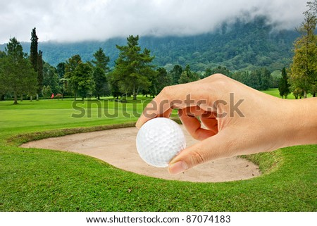Hand holding ball in Golf course on the hill at Bali , Indonesia