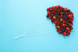Hand holding balloons made of berries on blue paper background. Healthy eating concept. Flat lay.