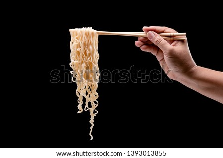 Hand holding bamboo chopsticks and fork over instant noodles. Studio shot isolated on black background