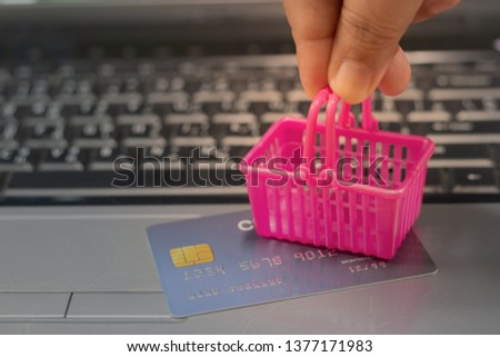 Hand holding basket shopping on mock up of credit card on laptop keyboard. Consumer can buy products directly anywhere anytime from seller using web browser. Online shopping and e-commerce concept.