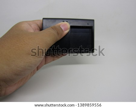 Hand holding battery camera dslr digital black charger isolated on white background. Important equipment to recharge
