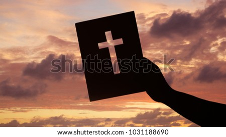 hand holding bible against afterglow