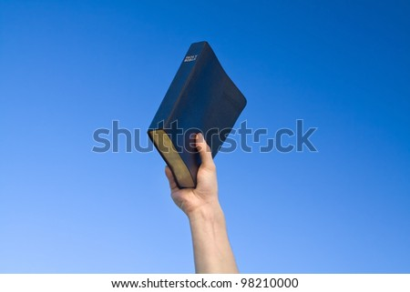 Hand holding Bible over blue sky
