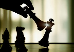 Hand holding black king attack white king of chess silhouettes battle on board. Black king are leader to fight with teamwork to victory. Leader,strategy and checkmate concept for success.