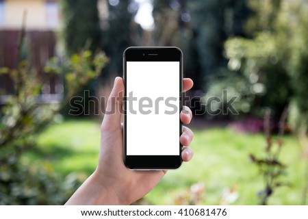 Hand holding black smartphone with blank screen against blurred garden background