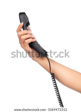 hand holding black telephone isolated on white background #1069472312