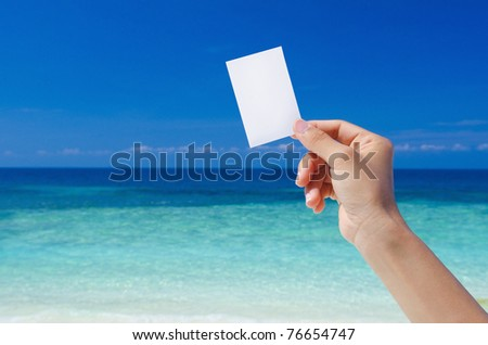 Hand Holding Blank Card, tropical beach as background