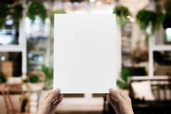Hand holding blank paper poster design for menu at restaurant, Mock up space for display of menu or design.