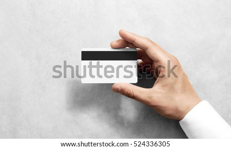 Hand holding blank white credit card mockup with black magnetic stripe, back side view. Plastic bank-card design mock up with magstripe. #524336305