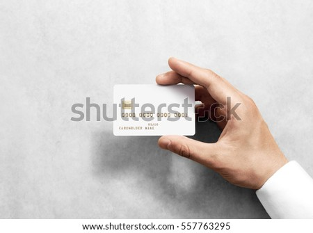Hand holding blank white credit card mockup with chip and embossed gold info. Plain plastic bank-card display front, design mock up. Electronic money holder template.