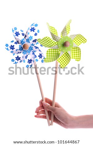 Hand holding blue and green pinwheel on the white background