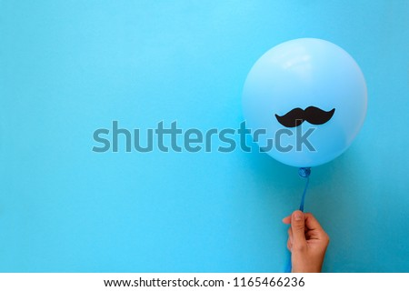Hand holding blue balloon with a paper mustache on blue paper background. Cut out style. Father's day or man health concept. Top view. Copy space