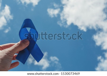 Hand holding blue ribbon on blue sky background , Colorectal cancer, Prostate Cancer Awareness, Movember Men health awareness, November blue, International Men's Day, world diabetes day