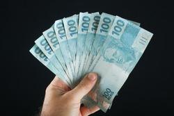 Hand holding Brazilian money. 100 reais banknotes. Black background.