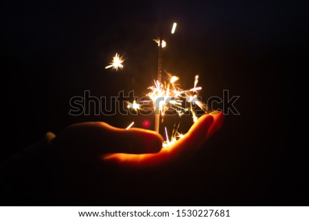 Hand Holding Bright Burning SParkler Celebrating The Festive Season, Joy And Cheerful Concept, Holidays And Festivities, 4th Of July And Christmas  And New Year Background