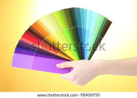 hand holding bright palette of colors on yellow background