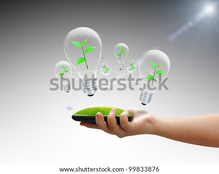 Hand holding bulb with green tree