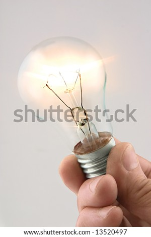 Hand holding burning electric lamp