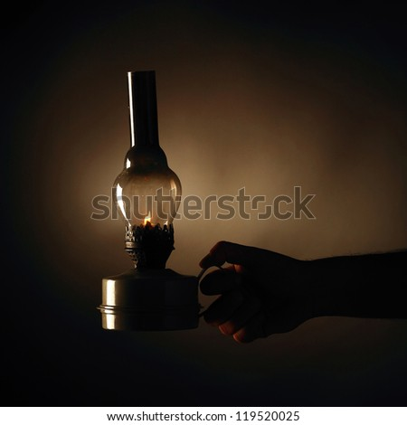 Hand holding burning old betty lamp