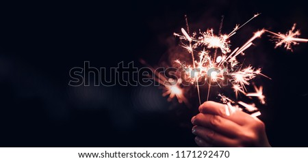 Hand holding burning Sparkler blast on a black bokeh background at night,holiday celebration event party,dark vintage tone