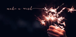 Hand holding burning Sparkler blast with make a wish word on a black bokeh background at night,holiday celebration event party,dark vintage tone.copy space for adding text