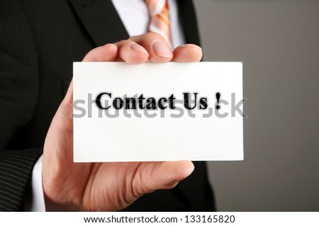 hand holding business card with the message contact us - stock photo