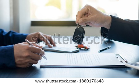 Hand holding car keys and car rental concept A close-up view of the agent, giving the customer the car keys after signing the lease, rental form and car name. Imagine de stoc ©