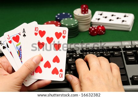 hand holding cards with computer keyboard chips and dices in background