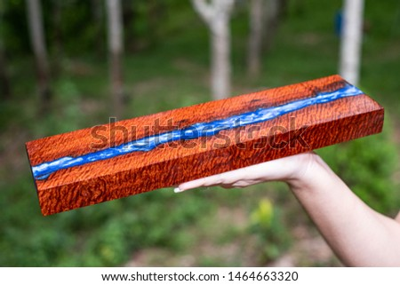 Hand holding casting resin wood has tiger stripe or curly stripe grain, wooden exotic beautiful pattern for crafts or abstract background texture #1464663320
