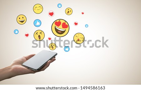 Hand holding cellphone with emotive on subtle background. Communication and emotion concept