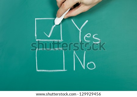Hand holding chalk making a yes choice