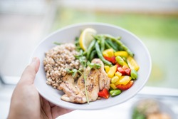 Hand holding chicken and buckwheat dish with green beans, broad beans, tomato, and pepper slices. Nutritious dish with vegetables and chicken on white plate. Healthy balanced diet
