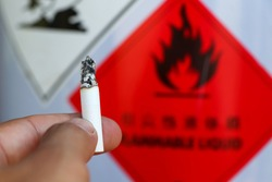 Hand holding cigarettes near flammable objects