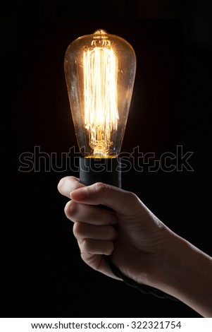 Hand holding classic Edison light bulb on black background with space for text #322321754