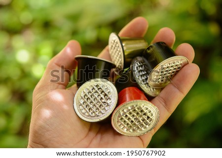 Hand holding coffee capsules used to be discarded with defocused foliage background. Foto stock ©