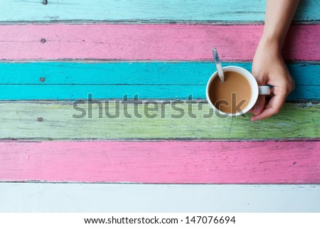 hand holding coffee cup on colorful coffee table