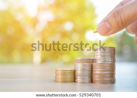 Hand holding coin with white piggy bank and home on old wood tree bokeh background.concept save money