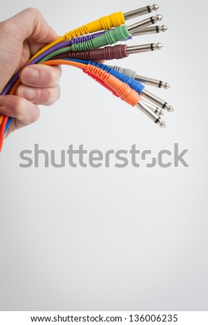 Hand holding color wires on a white background