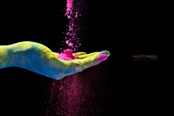 Hand holding colorful powder cupped in the palm for Holi festival of colors. Closeup over a black background with copy space.