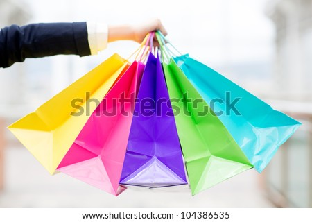 Hand holding colorful shopping bags at the mall