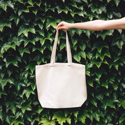 Hand holding craft linen eco bag in the garden among plants. Eco-friendly concept of consumption and shopping.