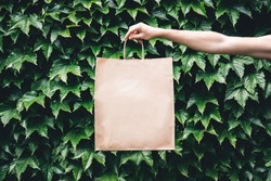 Hand holding craft paper eco bag in the garden among plants. Eco-friendly concept of consumption and shopping.