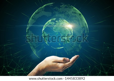 Hand holding creative polygonal globe on blue backdrop. Interactive map and AI concept