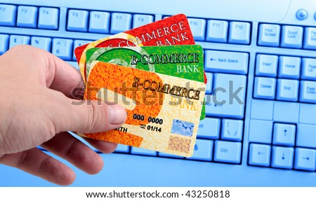 Hand holding credit card in front of computer keyboard