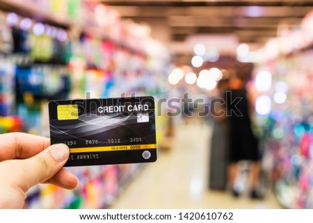 Hand holding credit card with blur supermarket, shopping and retail concept