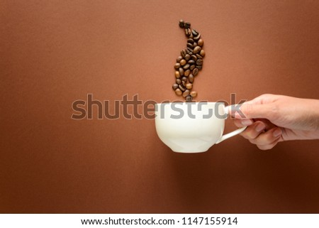 Hand holding cup of coffee with smoke from coffee beans brown paper background. Top view. Flat lay. copy space. Good morning concept.