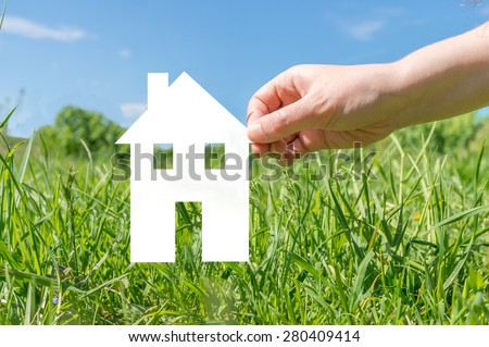 Hand holding cut off white paper house in nature as symbol of mortgage